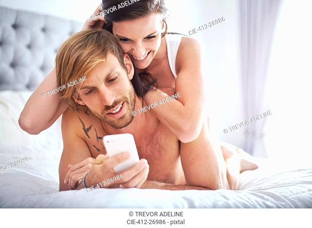Couple laying on bed texting with cell phone