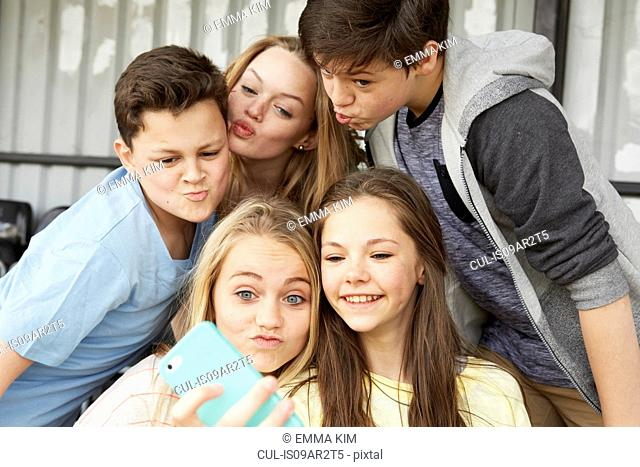 Five boys and girls making faces for smartphone selfie in shelter