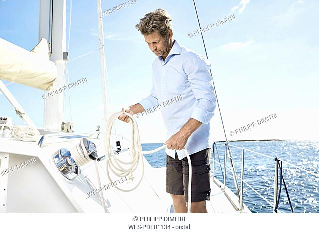 Mature man with rope on his sailing boat
