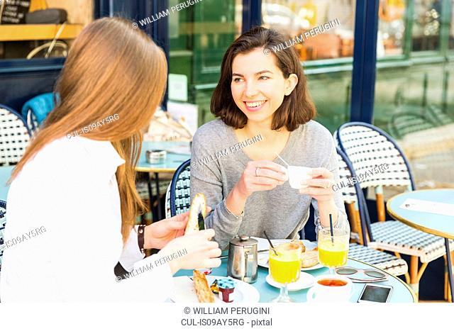 Two young women drinking breakfast espresso at sidewalk cafe, Paris, France