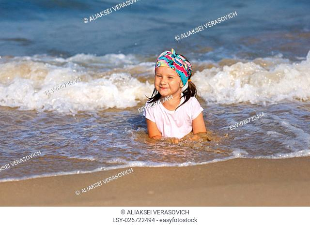 Smiling child in a white t-shirt lying in water on the beach. Shallow depth of field. Focus on the model's face