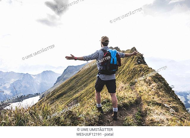 Germany, Bavaria, Oberstdorf, hiker in alpine scenery enjoying the view