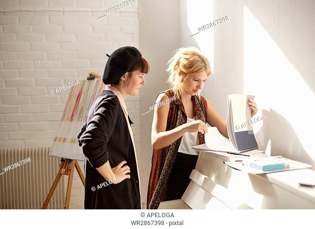 Young female painters discussing while looking at papers in studio