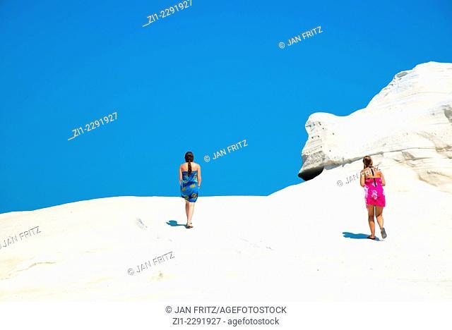 two teens walking on the white sandstone cliffs of Sarakiniko beach at milos, Greece