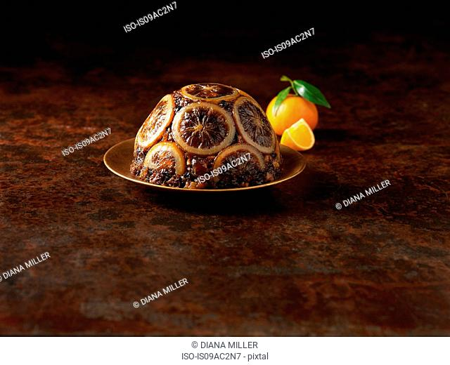 Christmas pudding decorated with sliced oranges
