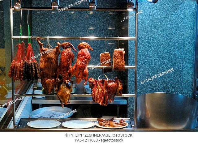 Assorted meat, ducks, a pig and sausages in a Thai food shop