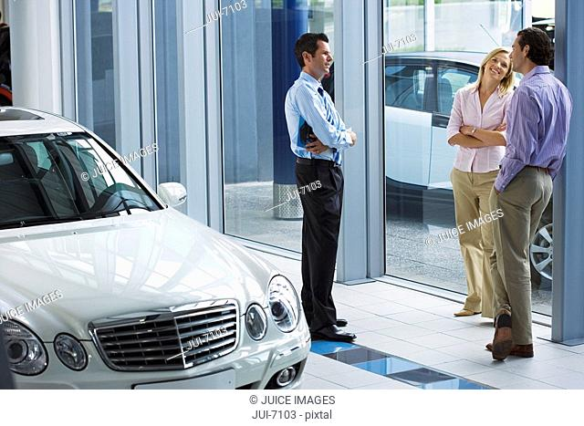 Car salesman talking to couple near new car in showroom, smiling