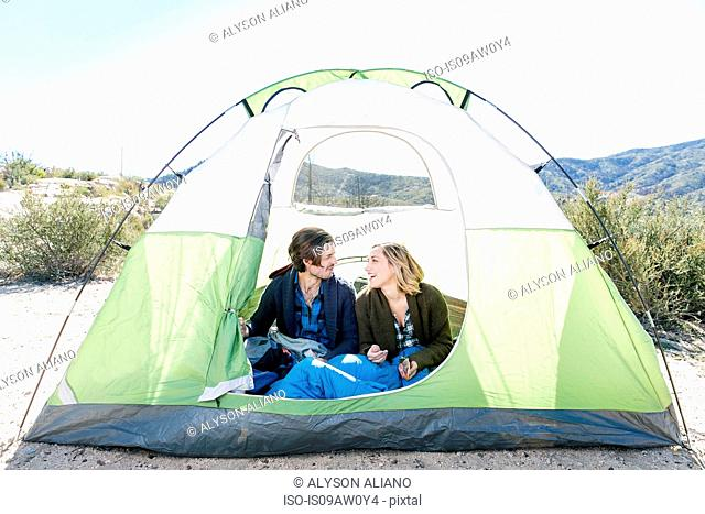 Young couple sitting in tent in rural environment
