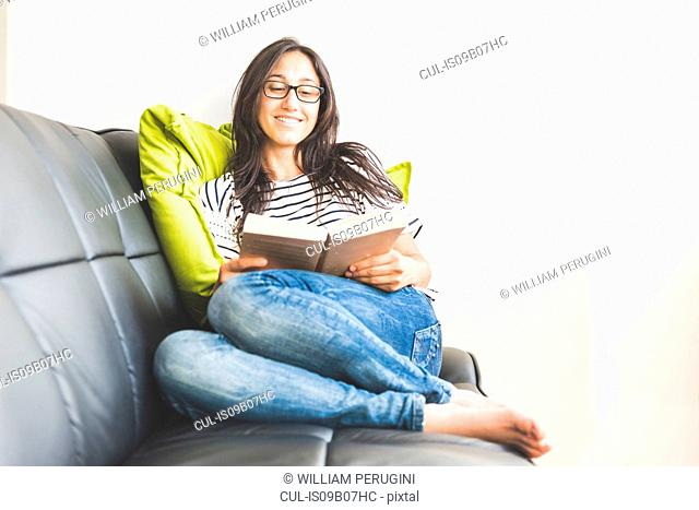 Woman sitting on sofa reading book smiling