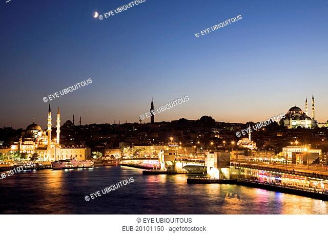 Sultanahmet. The Golden Horn. The New Mosque or Yeni Camii at left the Galata Bridge and Suleymaniye Mosque at right illuminated at dusk with crescent moon in...
