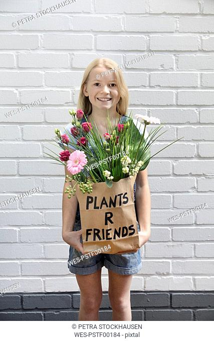 Portrait of smiling girl with paper bag of flowers