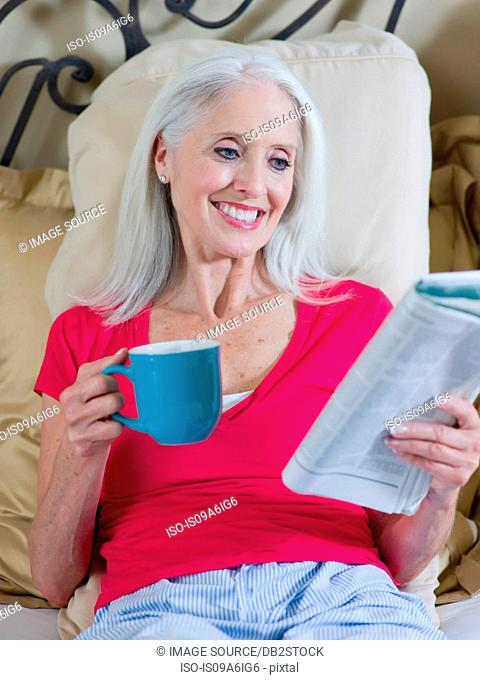 Older woman reading newspaper on bed