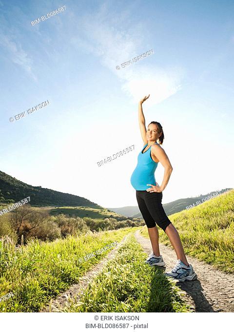 Pregnant Hispanic woman exercising in remote area