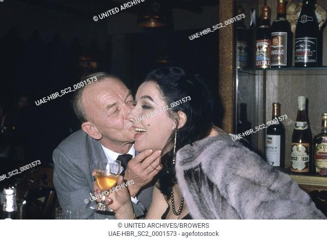 Der deutsche Schauspieler Hannes Messemer küsst die Ehefrau des Schauspielers Nino Korda, Deutschland 1980er Jahre. German actor Hannes Messemer kissing the...