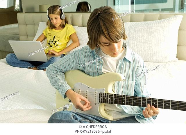 Boy playing a guitar and girl working on a laptop behind him