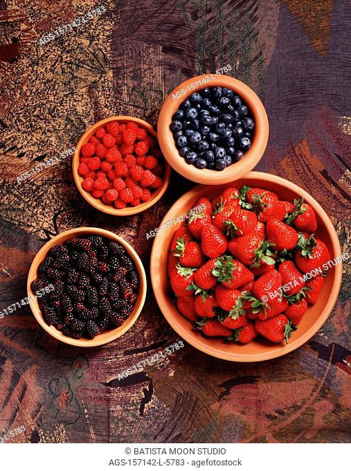 Agriculture - Bowls of raspberries, blueberries, strawberries and blackberries on a fabric background, studio