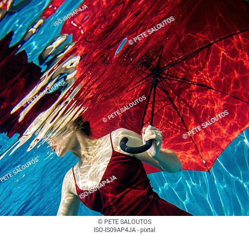 Mature woman wearing red dress, holding red umbrella, underwater view, mid section