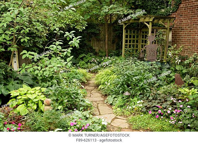 Flagstone path from brick patio leads through shade garden to arbor (Impatiens wallerana; Alchemilla mollis; Hakonechloa macra 'Aureola'; Helleborus x hybridus)