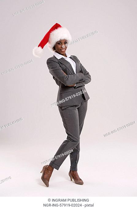 African American businesswoman wearing Santa Claus hat full length portrait on gray background