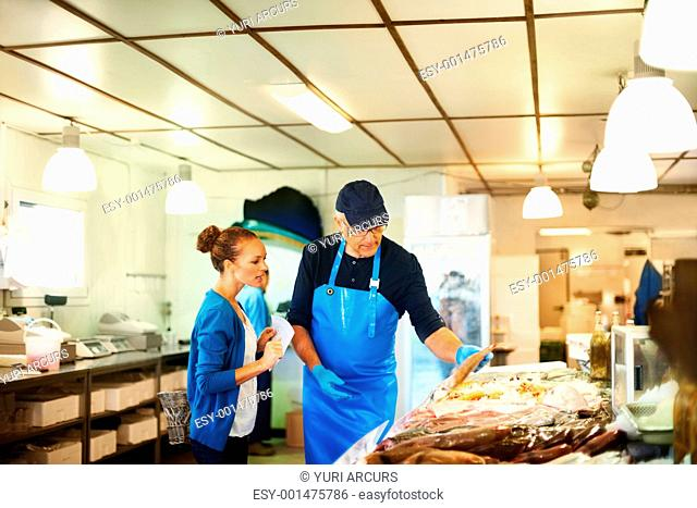 Fishmonger showing fish to a young woman