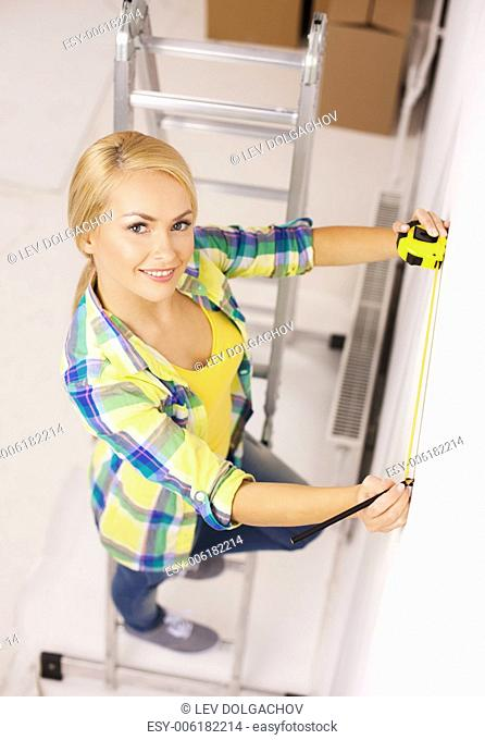 repair, building and home concept - smiling woman measuring wall
