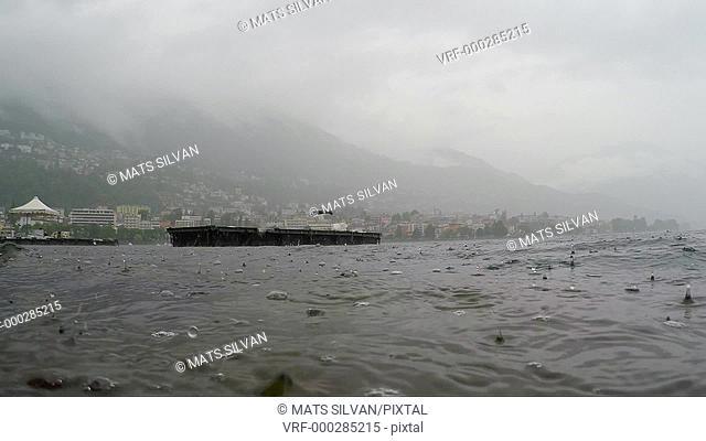 Rain in slow motion falling down on alpine lake Maggiore in Ticino, Switzerland