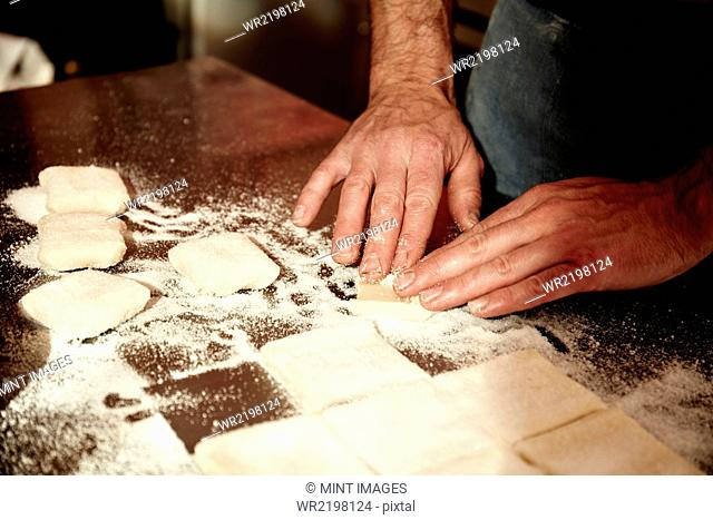 A baker working on a floured surface, dividing the prepared dough into squares