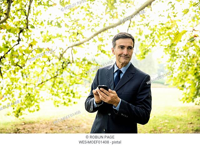 Smiling businessman with cell phone in a park