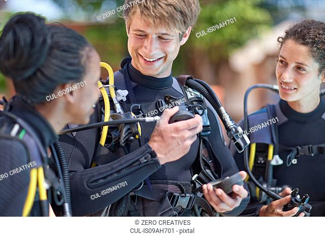 Scuba diving instructor demonstrating oxygen mask to female pupils