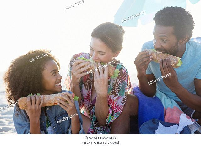 Playful multi-ethnic family eating baguette sandwiches on beach