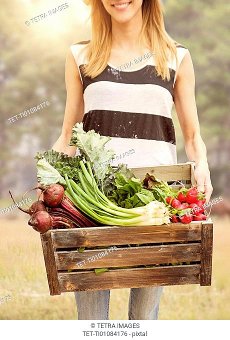 Woman carrying fresh vegetables in box