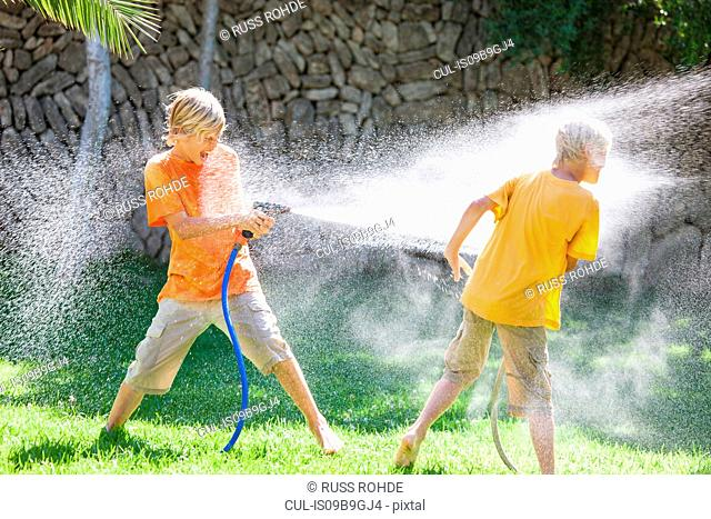 Boys in garden spraying each other with water from hosepipe