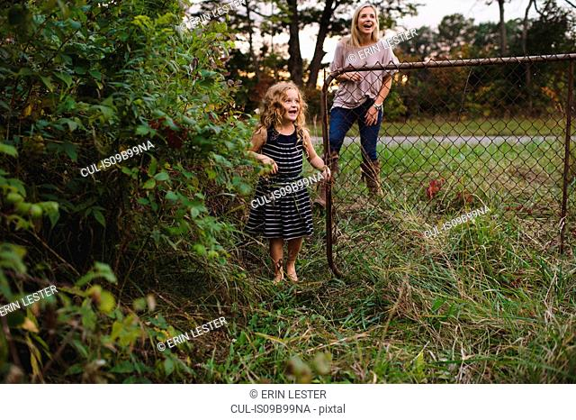 Mother and daughter entering farm gate