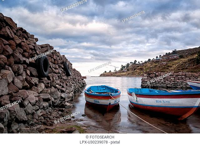 Lake Titicaca: Llachon peninsula, two fishing boats moored at sunrise, in harbour inlet, Peru
