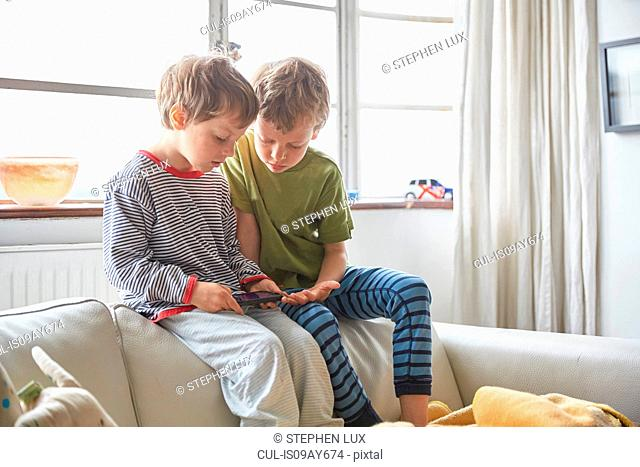 Boys wearing pyjamas sitting on sofa looking at smartphone