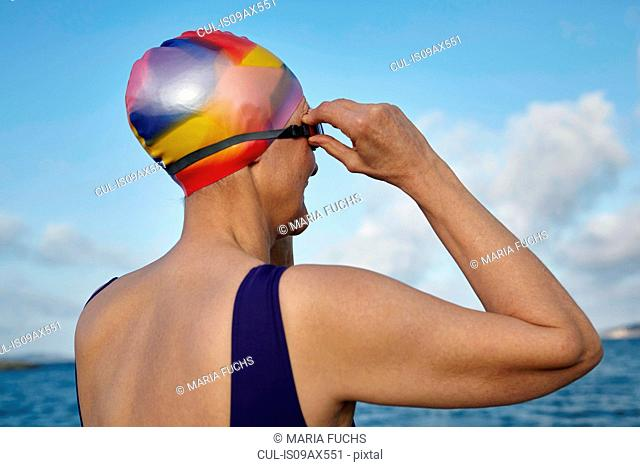 Mature woman wearing swimming costume and swimming hat, standing beside the sea, adjusting swimming goggles, rear view