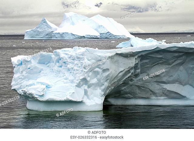Antarctica - Non-Tabular Iceberg Drifting In The Ocean - Antarctica In A Cloudy Day