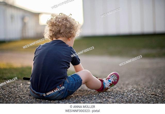 Little girl sitting on gravel path