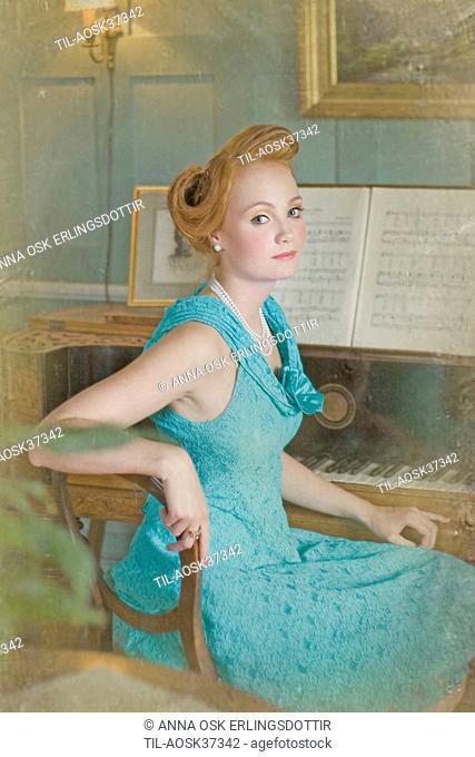 Lone female figure wearing blue dress sitting at piano keyboard