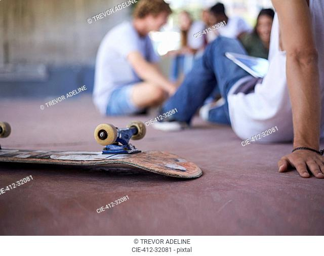 Skateboard upside-down next to teenage friends hanging out at skate park