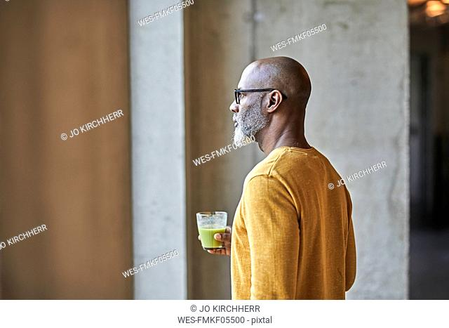 Mature businessman in office holding a smoothie at the window