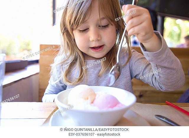 portrait of three years old blonde child ready to eat two scoops of strawberry and vanilla ice cream, in white bowl, with a spoon in raised hand