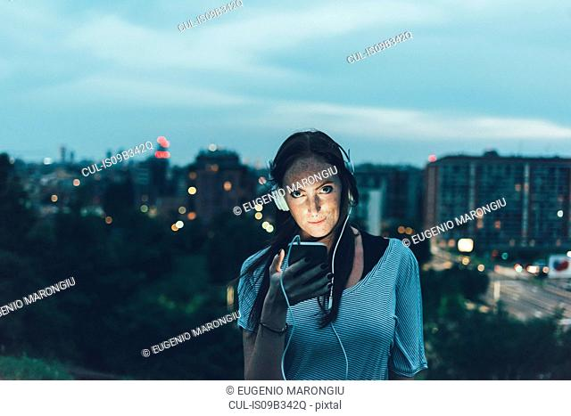 Portrait of young woman listening to headphones above city at dusk