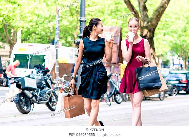 Two cheerful female best friends drinking coffee or juice while walking downtown for shopping in summer