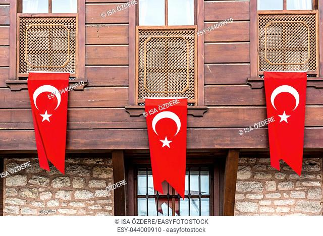 Three Turkish flag hanging on wooden house wall. Turkish flag concept