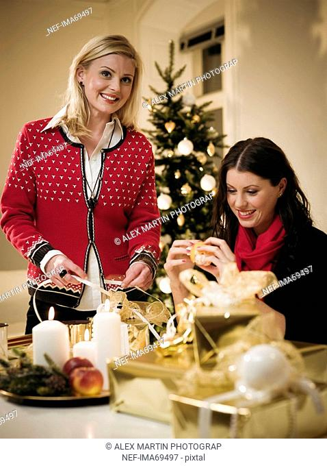 Two women wrapping Christmas gifts