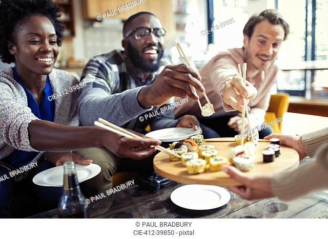 Friends enjoying sushi in restaurant