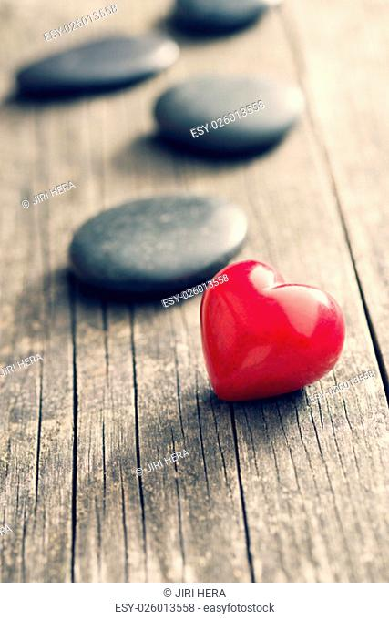 red stone heart on old wooden background