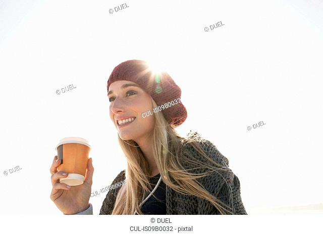 Young woman holding cup of coffee on cold day
