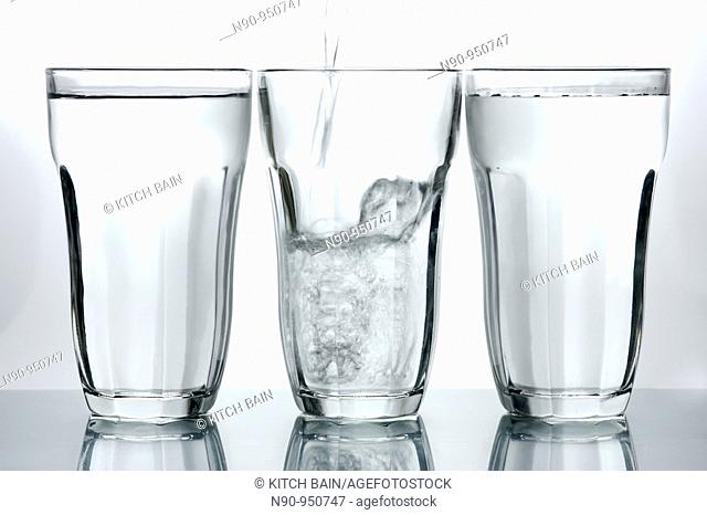 Glasses of drinking water backlit against a white background